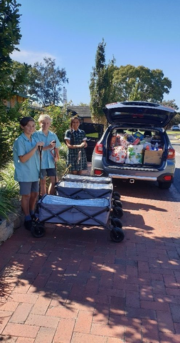 Students with a donation of food in wagons near a car