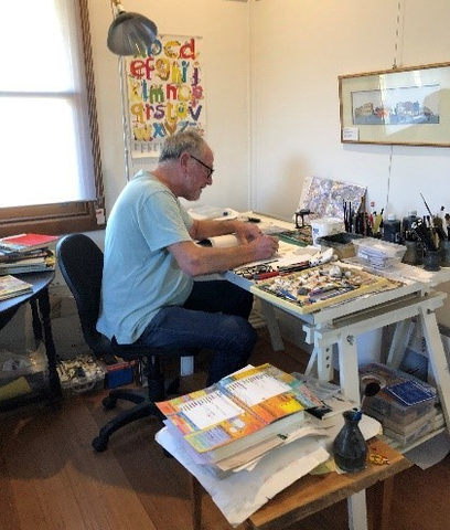 Man working on art at a drawing table