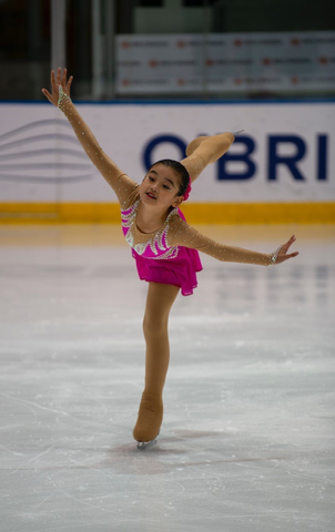 Young girl figure skating in a pink costume