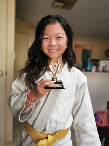 Young girl holding a Judo trophy
